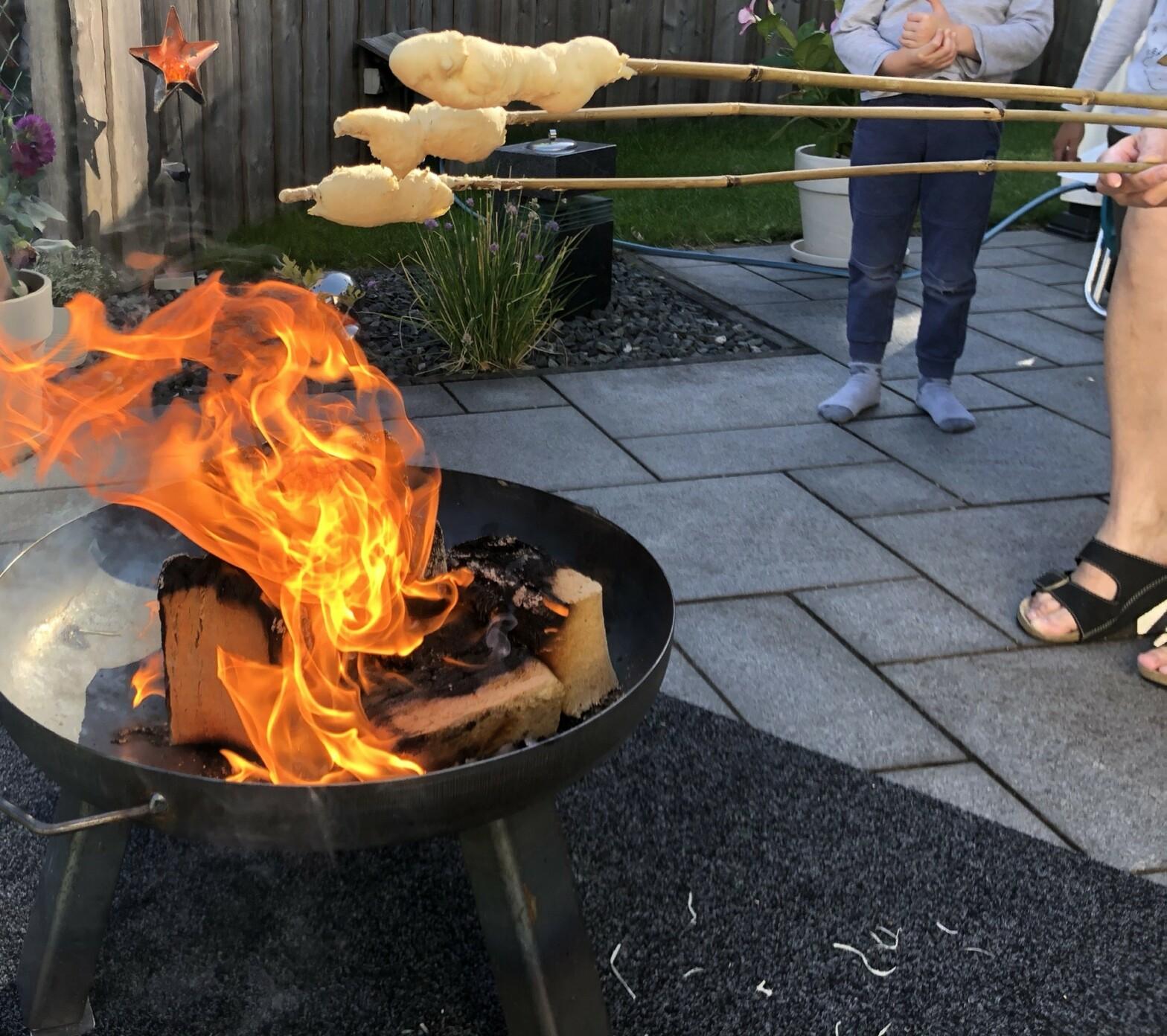 Die Feuerschale verbrennt Holzbriketts und steht sicher auf der Matte.